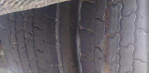 Nadmierne zużycie bieżnika opony oraz uszkodzony, widoczny kord opony.
