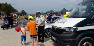 Inspektor promuje bezpieczeństwo w ruchu drogowym rozdając elementy odblaskowe.